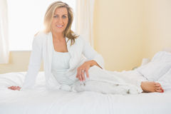 Content woman looking at camera posing on her bed Stock Images