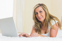 Content woman looking at camera using a laptop lying on a bed Stock Images