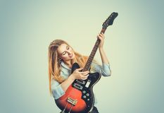 Content woman looking at electric guitar stock photo