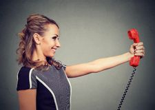 Content woman with red handset royalty free stock photos