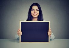 Content woman showing blank blackboard stock photography