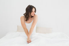 Content woman sitting and looking away in bed Stock Images