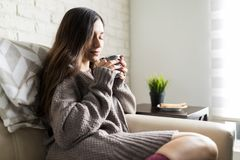 Content Woman In Sweater Taking Aroma Of Fresh Tea. Brunette woman smelling refreshing tea during cold morning stock photography