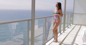 Content woman in swimsuit posing on balcony stock video