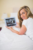 Content woman using a tablet pc lying on her bed Stock Photos