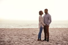 Content young African couple standing on a beach at dusk. Content young African couple looking into each other`s eyes while standing together on a sandy beach at royalty free stock image