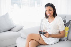 Content young dark haired woman in white clothes playing video games Stock Photos