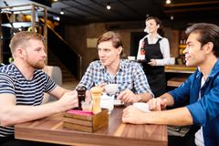 Content young friends chatting over tea in cafe. Group of content young friends in casual clothing sitting at table in modern cafe and drinking tea from cups stock photos