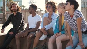 Content young friends chilling on city seafront stock footage