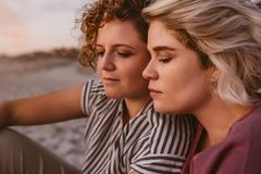 Young lesbian couple enjoying a romantic beach sunset together stock image