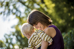 Content young mother carrying and hugging her baby boy Stock Image