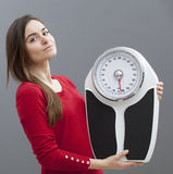 Content young woman holding scales. Health and fitness - chic 20s girl standing next to her weighting scale for kilos or pounds control stock photo