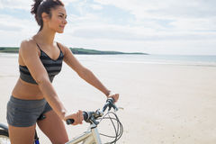 Content young woman riding her bike on the beach Stock Photos