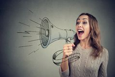 Cheerful woman sharing with news using loudspeaker. Content young woman screaming in loudspeaker making announcement royalty free stock images