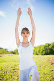 Content young woman stretching outside. In a sunny meadow Stock Images