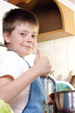 Contented boy at kitchen. Showing thumb up gesture Stock Image
