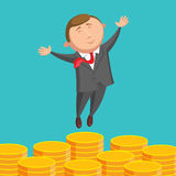 Contented businessman is jumping above gold coins Stock Photo
