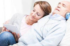 Contented couple spending a relaxing day together. With the wife browsing on a tablet pc and men listening to music on headphones Stock Images