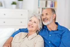Contented elderly couple sitting reminiscing. Contented elderly couple sitting in a close embrace in their living room reminiscing and recalling happy nostalgic Royalty Free Stock Image