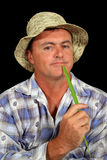 Contented Farmer. Holding a blade of grass Royalty Free Stock Image