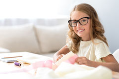 Contented girl sewing and looking at camera Stock Photos