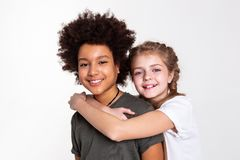 Contented good-looking kids spending time together in studio. Widely smiling. Contented good-looking kids spending time together in studio and closely contacting royalty free stock images