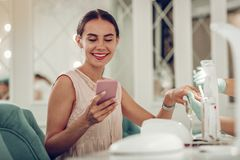 Contented good-looking middle-age woman checking her smartphone stock photos