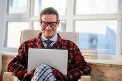 Happy adult male working on laptop indoors. Contented guy sitting in chair and smiling in bedroom. He is looking at computer with satisfied look Royalty Free Stock Photo