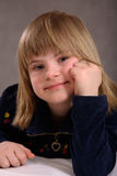 Contented Handicapped Girl. Cute, happy, contented blond 9-year old girl with Downs Syndrome poses for this nice studio portrait Stock Photo