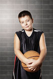 Contented kid holding basketball Royalty Free Stock Images
