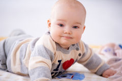 Contented little baby smiling at the camera Royalty Free Stock Image
