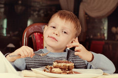 Contented little boy eating cake for dessert Stock Photo