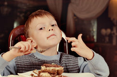 Contented little boy eating cake for dessert Stock Photography