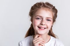 Contented little pretty kid showing her teeth in wide smile. Photographing in studio. Contented little pretty kid showing her teeth in wide smile and touching royalty free stock photos