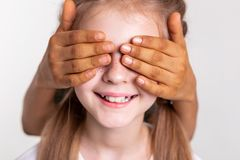 Contented pale girl with bright freckles having closed eyes. Boy closing eyes. Contented pale girl with bright freckles having closed eyes with hands of her royalty free stock photos