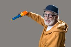 Contented pensioner having fun with toy Royalty Free Stock Photos