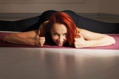 Contented redhead at split yoga pose. Raising both thumbs up Royalty Free Stock Photos