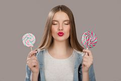 Contented woman with big colorful lollipop. The concept of sweets. Gray background stock images