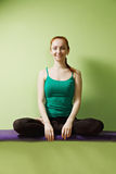 Contented woman in lotus pose. Contented redhead caucasian woman sitting in lotus yoga pose at the green wall Royalty Free Stock Image
