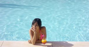 Contented woman at pool edge with drink stock video