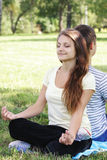 Contented woman relaxing in yoga pose. Leaning on friend back Stock Images