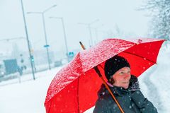 Contented woman talking on mobile phone under umbrella in snow. Contented woman talking on mobile phone under red umbrella while standing in the street in winter stock photo