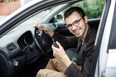Contented young driver is sitting at his car while looking at the camera. He is holding the keys at his left hand. His right hand. Is on the steering wheel stock photo