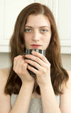Contented young woman. With cup of tea or coffee in the kitchen Stock Image