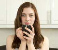 Contented young woman with cup of tea or coffee Royalty Free Stock Image