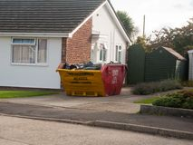 Contentor acima enchido dos desperdícios da faixa clara fora do pavimento da casa fotos de stock royalty free