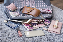 The contents of the female handbag. Phone, tablet ,notebook, lipstick, perfume ,watch,lipstick,eyeglasses stock images