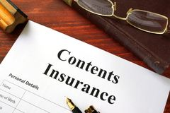 Contents insurance policy on a wooden surface. Royalty Free Stock Photo