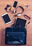 The contents of a modern business briefcase on a wooden desk. Stock Photos