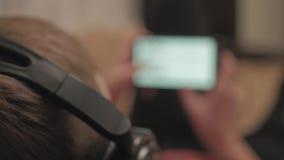 Contenu de observation de médias de garçon utilisant des écouteurs et l'appli de téléphone portable se trouvant sur le divan à la clips vidéos